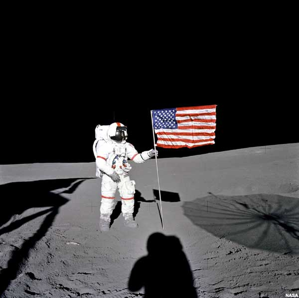 February 12. Darwin Day. A Reason to Celebrate Creation. Astronaut Alan Shepard is pictured on Moon. The Moon surface is seen illuminated. The Sky is Dark. The Sky is also Dark in the rest of the Universe. Earth is one of its own kind original celestial object with its Blue Sky.