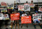 """Protesters display placards during a rally at the Chinese Consulate at the financial district of Makati city, east of Manila, Philippines Friday, April 17, 2015 to protest moves by China in """"fortifying"""" its claims at the disputed Spratlys group of islands in the South China Sea. The protesters led by Congressman Nery Colmenares urge China to """"stop its  reclamation activities in the Mischief Reef"""" which they claim to be still within the Philippines' EEZ (Exclusive Economic Zone). (AP Photo/Bullit Marquez)"""