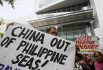 """Protesters display placards during a rally at the Chinese Consulate at the financial district of Makati city east of Manila, Philippines Friday, April 17, 2015 to protest against Beijing's land reclamation activities on disputed territory in the South China Sea. The protesters led by Congressman Nery Colmenares urge China to """"stop its reclamation activities in the Mischief Reef"""" which they claim to be still within the Philippines' EEZ (Exclusive Economic Zone). (AP Photo/Bullit Marquez)"""